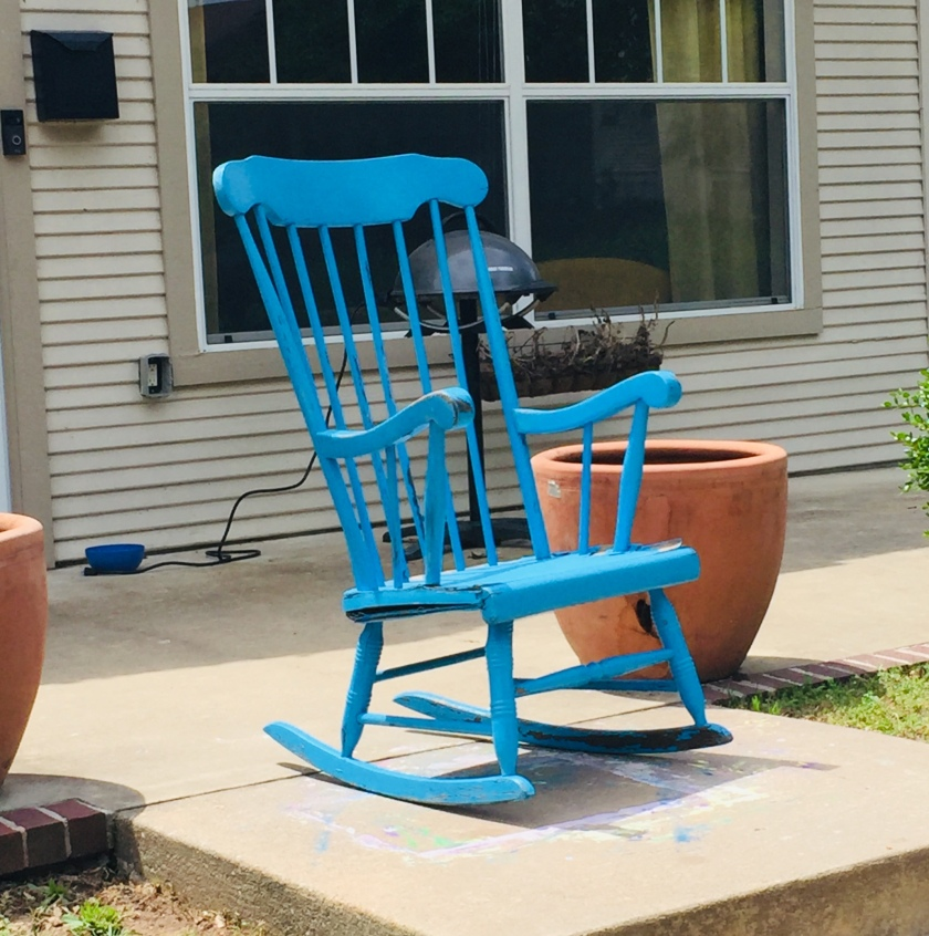 a bright blue wood rocking chair on a porch