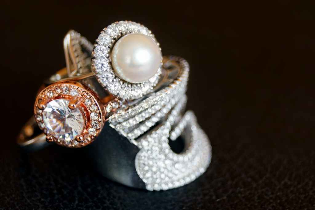 a white pearl ring with diamond highlights