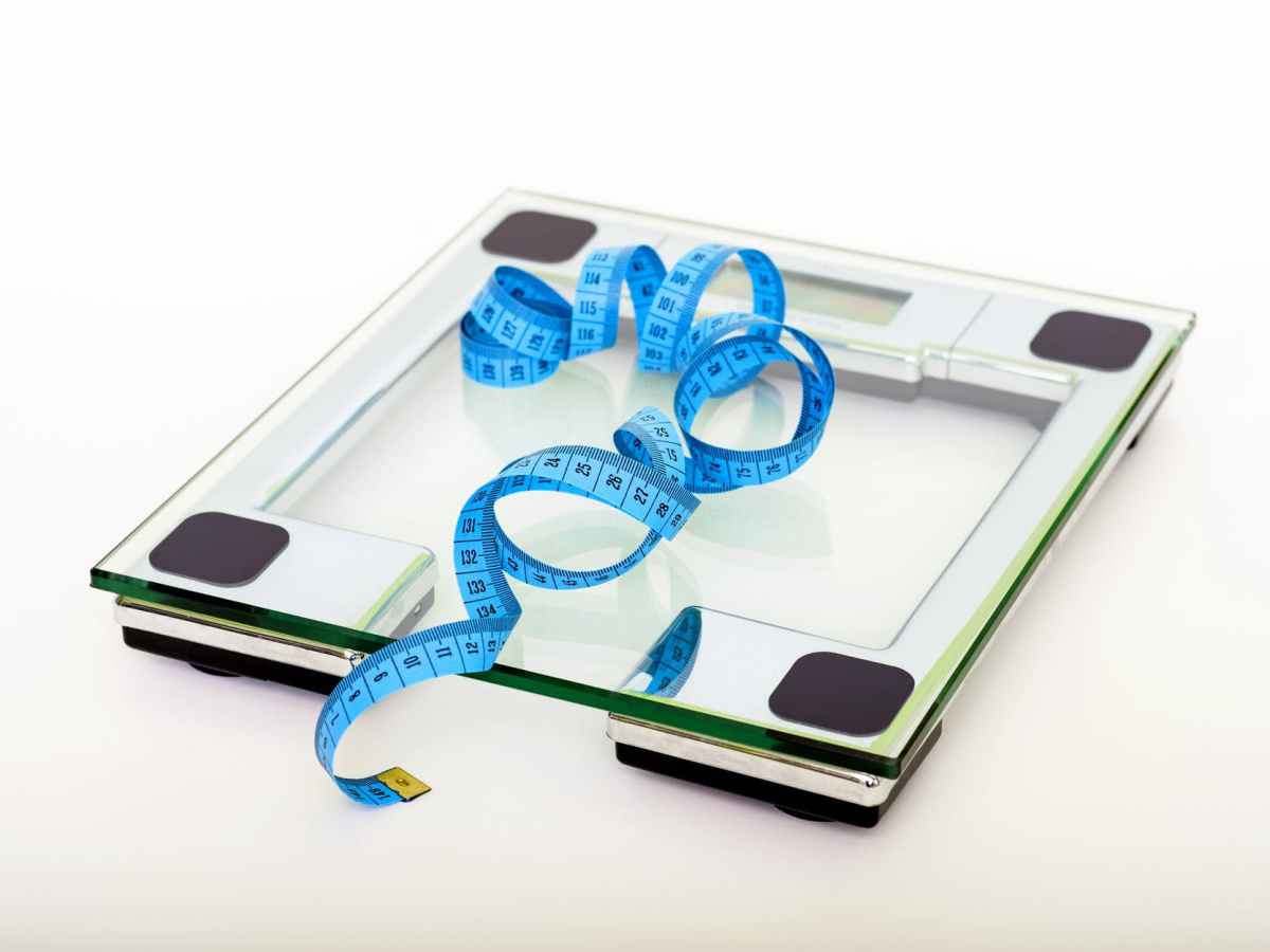 blue tape measure lying on clear glass square weighing scale