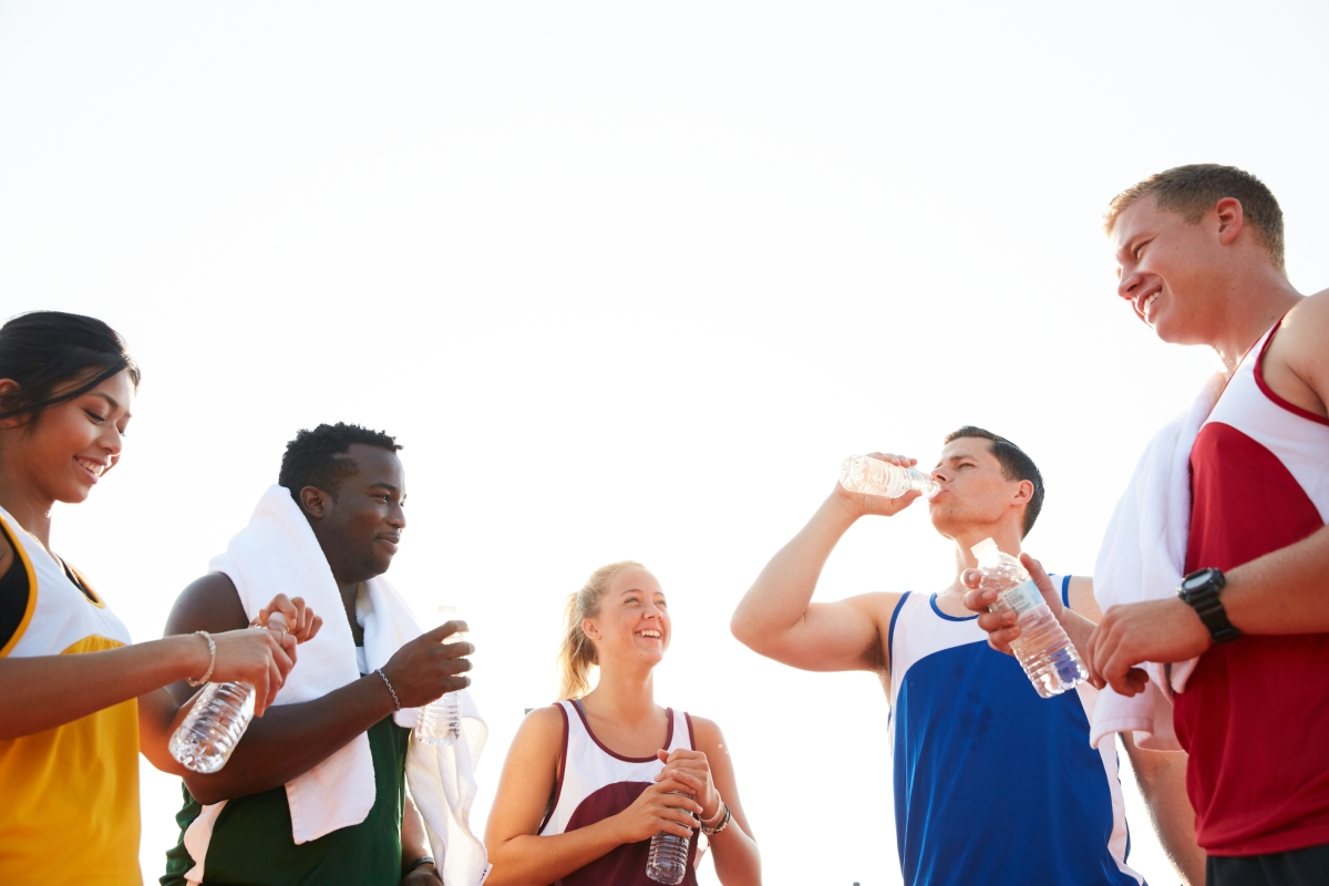 male and female athletes drinking bottled water