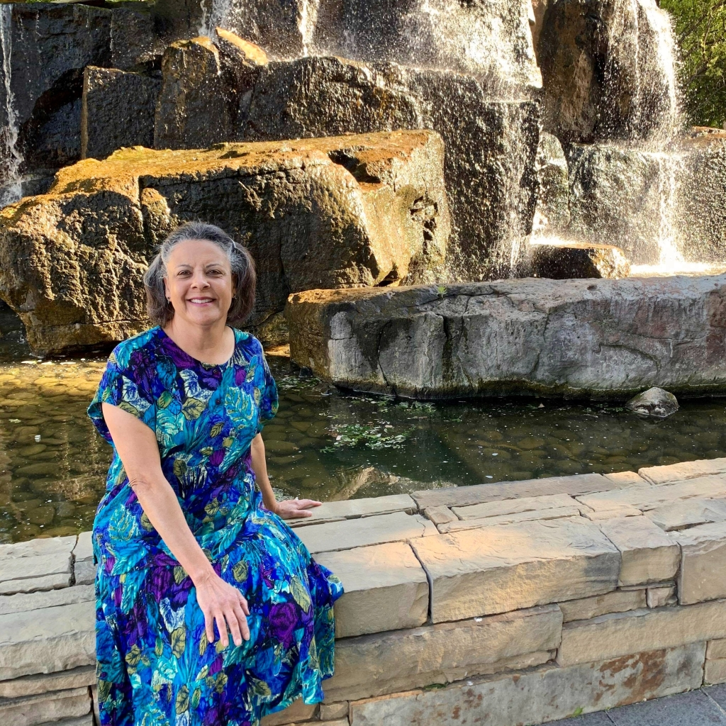 Dr Aletha in a print dress sitting by a waterfall