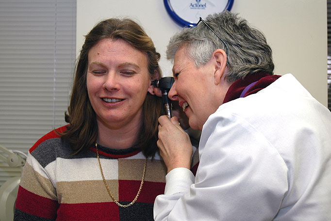 a woman doctor examining a women's ear