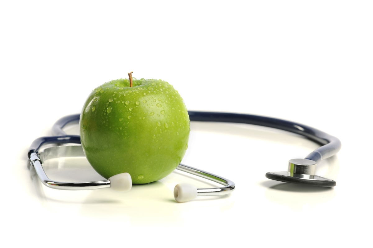 a Stethoscope and a green Apple