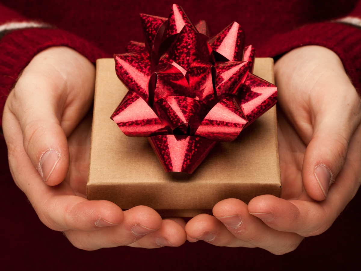 hands holding a small box with a red bow