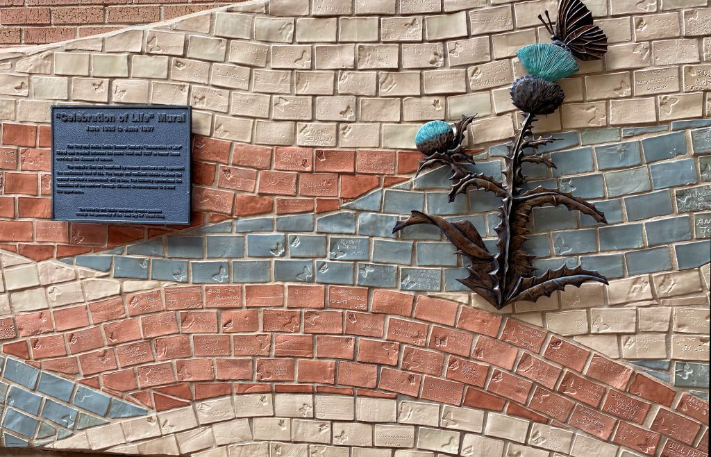 a wall decorated with inscribed bricks and a metal floral sculpture