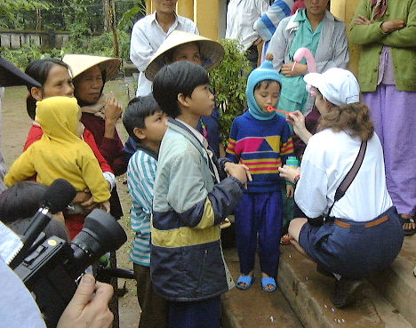 Vietnamese children with an American woman, blowing bubbles