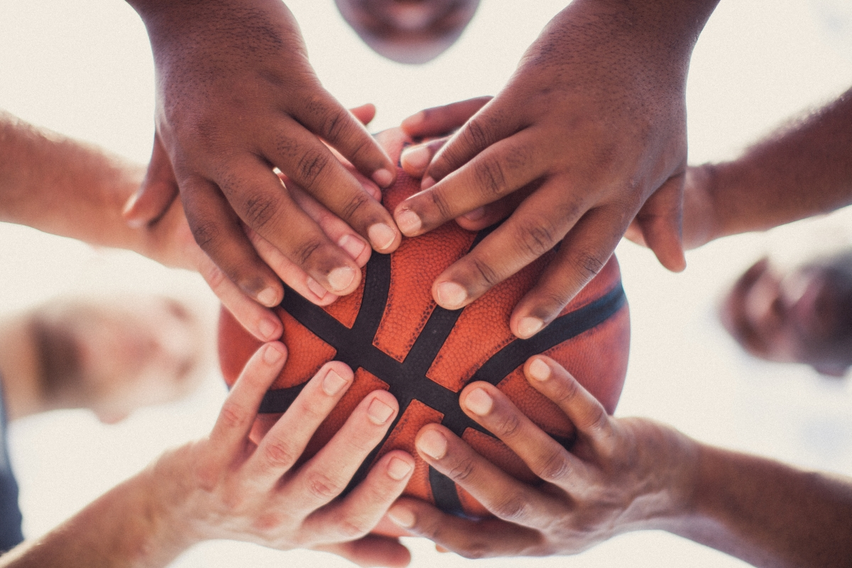 the hands of several people holding a basketball