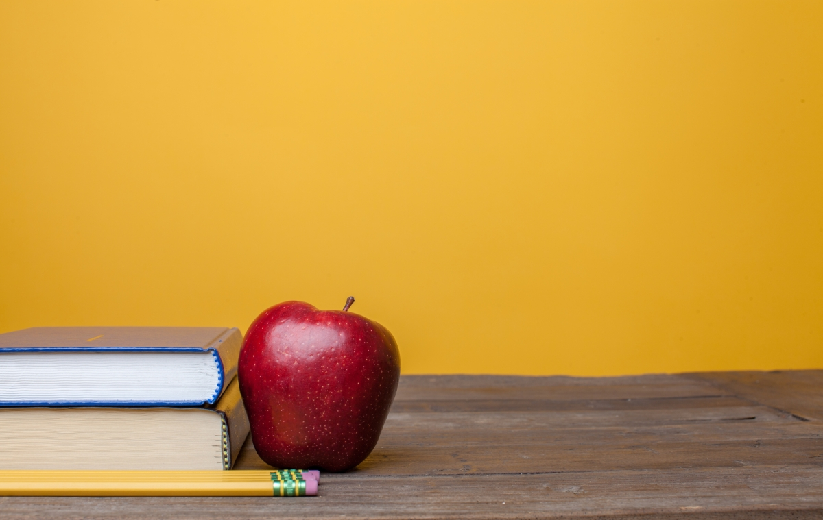 2 books stacked next to an apple l
