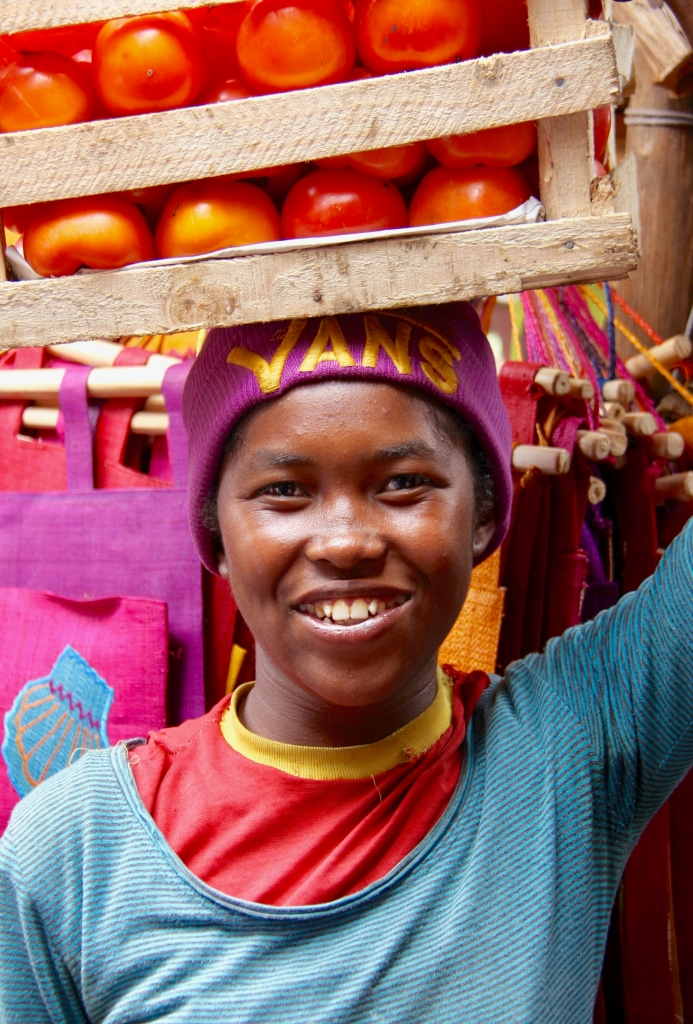 A young African woman with a crate of tomatoes on her head